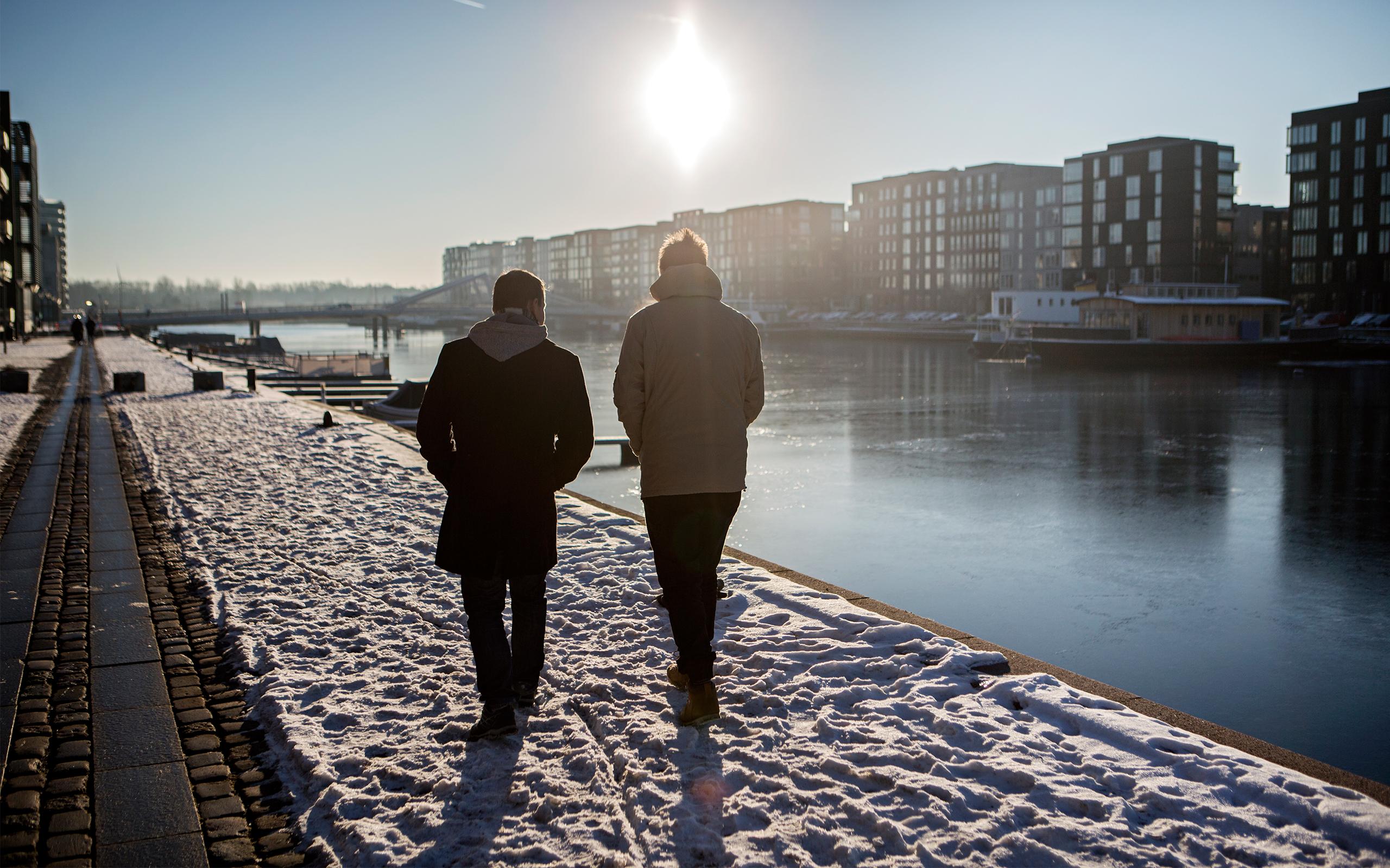To mennesker gå langs havnefronten ved Islands Brygge