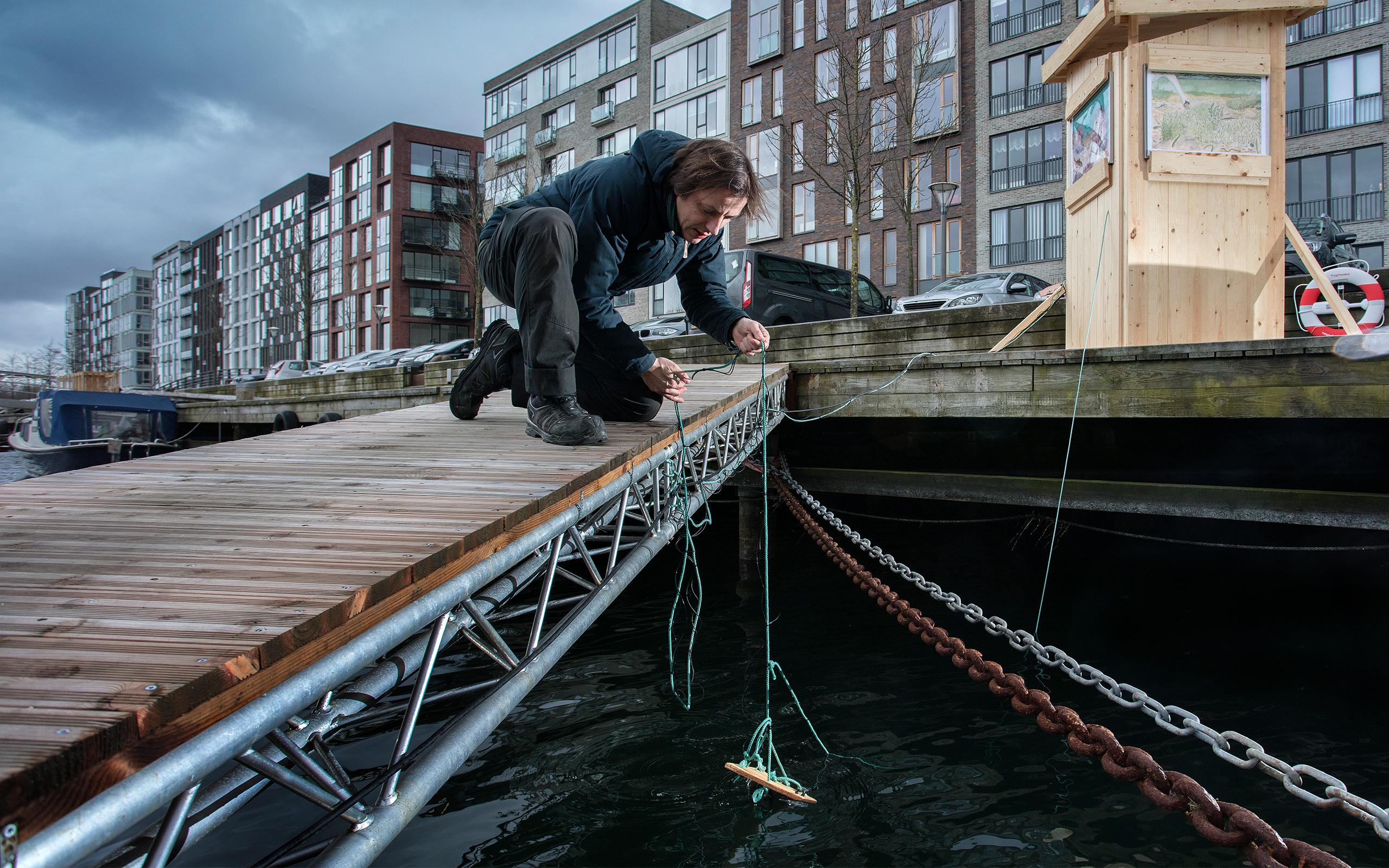Christian Liljedahl sætter et undervandskamera i vandet ved Sluseholmen